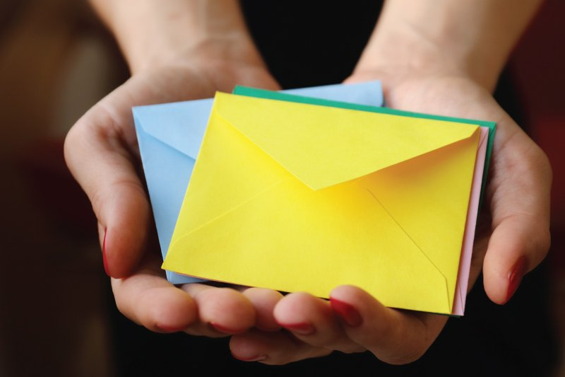 hands holding colored envelopes