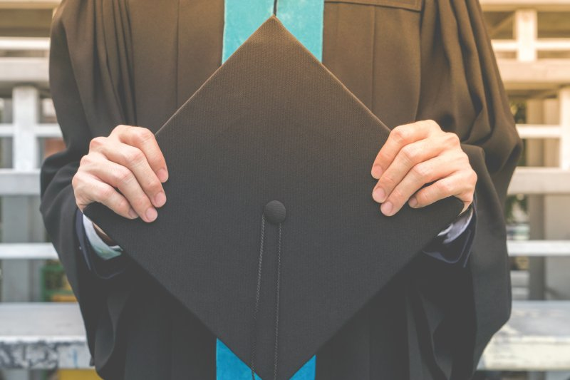male student holding graduation cap