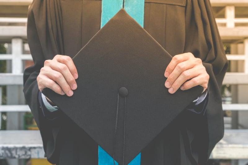 man graduating holding cap