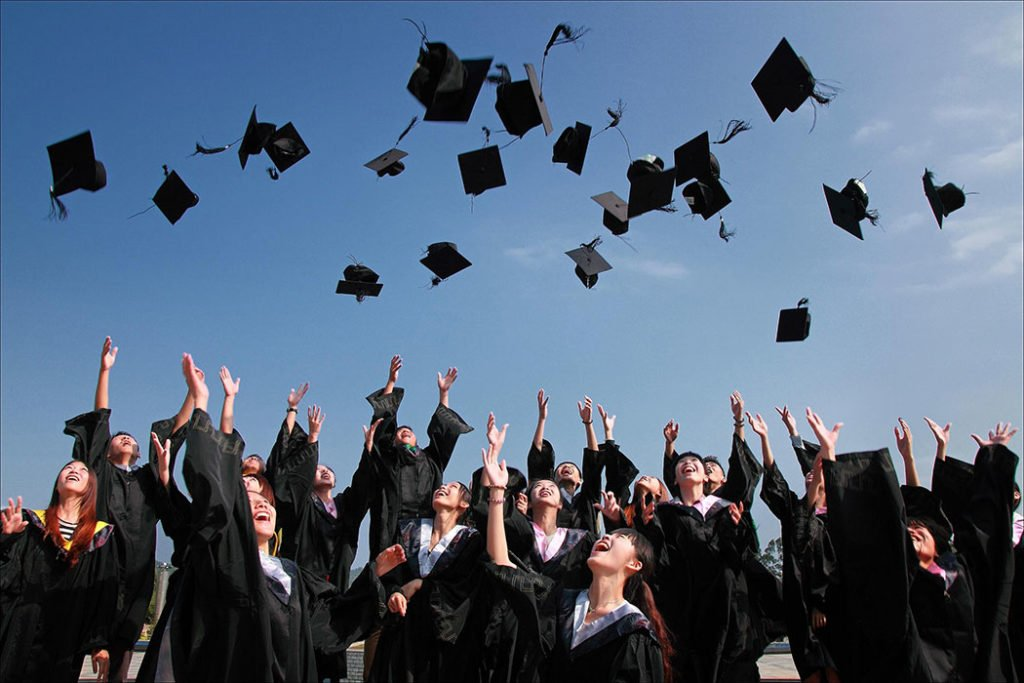 graduates tossing their caps outside