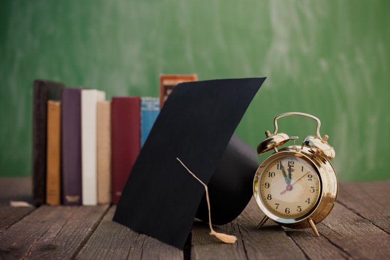 alarm clock, graduation cap, books