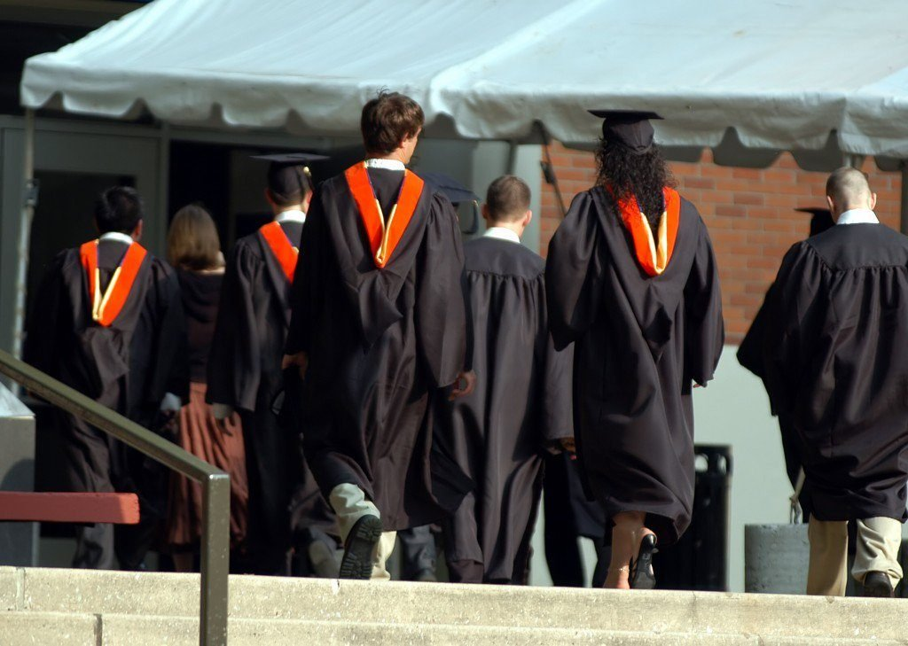 male and female graduates in black gowns, back view