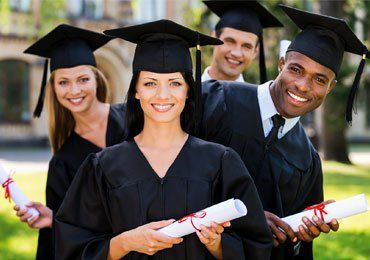 4 people smiling with cap, gown and diploma