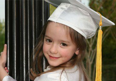 little girl wearing silver cap and gown with yellow tassel