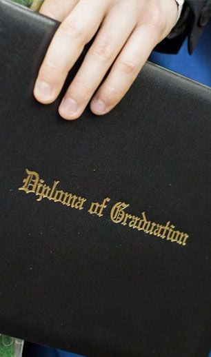 hand holding black diploma of graduation
